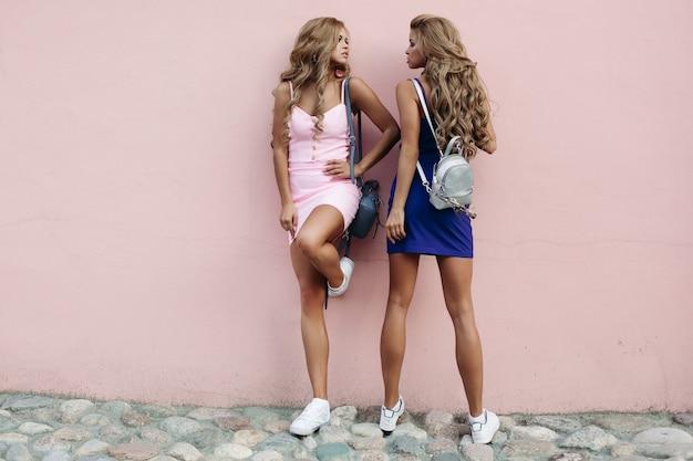 Bellissime modelle che si guardano l'un l'altro e che posano vicino al muro rosa