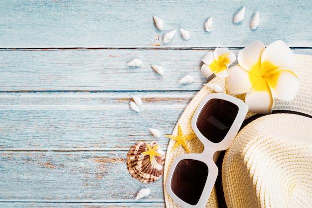 Bellissime vacanze estive, accessori da spiaggia, occhiali da sole, cappello e conchiglie su fondo in legno