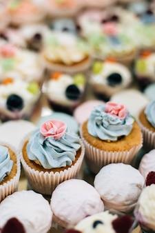 Bellissimi cupcakes colorati e dessert alla panna sul tavolo di catering per la festa