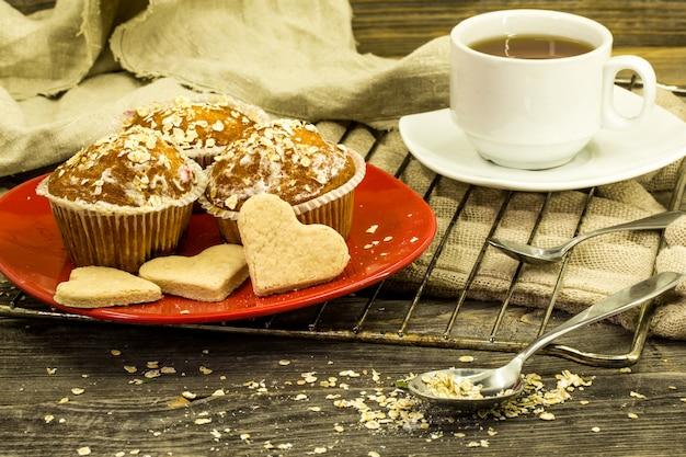 Bellissimi cupcakes con bacche sul tavolo di legno nel piatto rosso