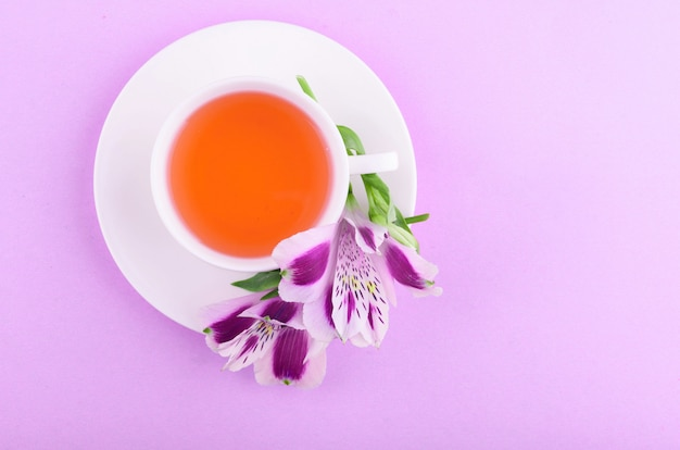 Bellissimi fiori di astromeria. tisana in una tazza bianca e un piattino bianco