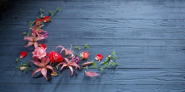 Bellissimi fiori estivi sul bordo di legno blu scuro