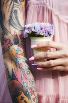 Bellissimi fiori nelle mani di una ragazza con tatuaggi