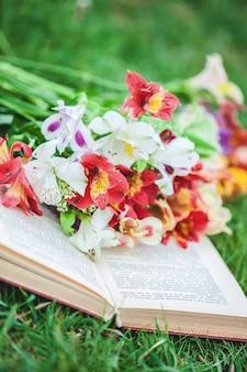 Bellissimi fiori sull'erba con un libro. avvicinamento