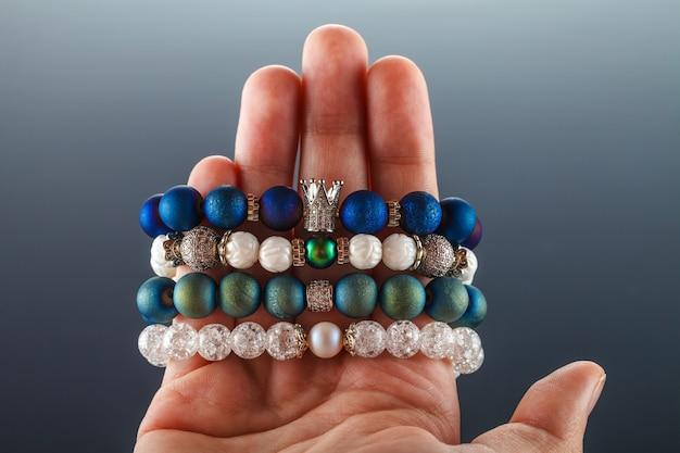 Bellissimi gioielli fatti di pietre naturali e accessori squisiti sulla mano di una donna