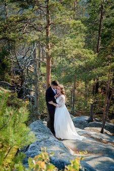 Bellissimi sposi che abbracciano sullo sfondo di rocce e montagne. sposa alla moda e bella sposa sono in piedi sulla scogliera. ritratto di nozze. foto di famiglia