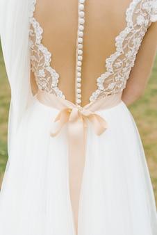 Bellissimo abito da damigella d'onore senza schienale con molti bottoni e fiocco beige