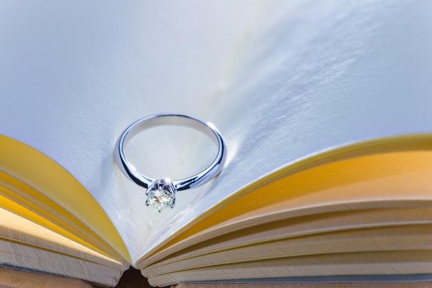 Bellissimo anello di diamanti su bianco libro aperto in tonalità di colore fresco e caldo