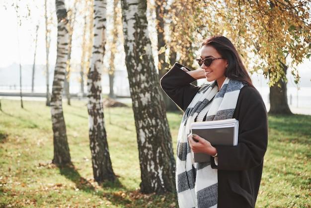 Bellissimo autunno il giovane castana sorridente in occhiali da sole sta nel parco vicino agli alberi e tiene il blocco note