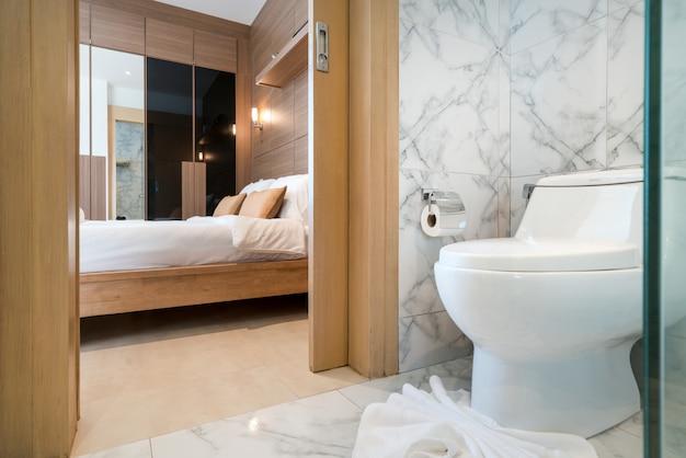 Bellissimo bagno interno reale bianco con water con camera da letto