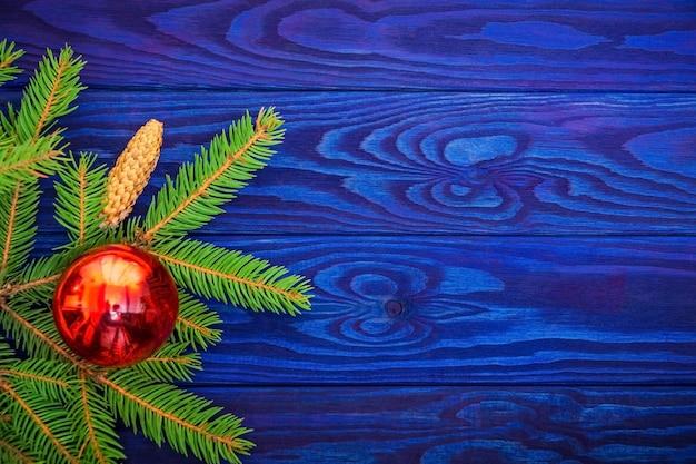 Bellissimo bordo di natale di abete rosso e giocattoli su uno spazio di legno blu