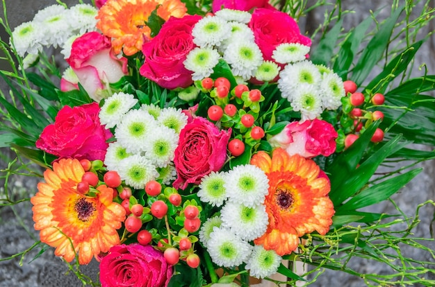 Bellissimo bouquet con rose rosa fresche, gerbere, margherite, iperico con gocce di rugiada