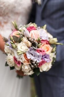 Bellissimo bouquet da sposa con fiori rossi, rosa e bianchi, rose ed eucalipti, peonie, calle.