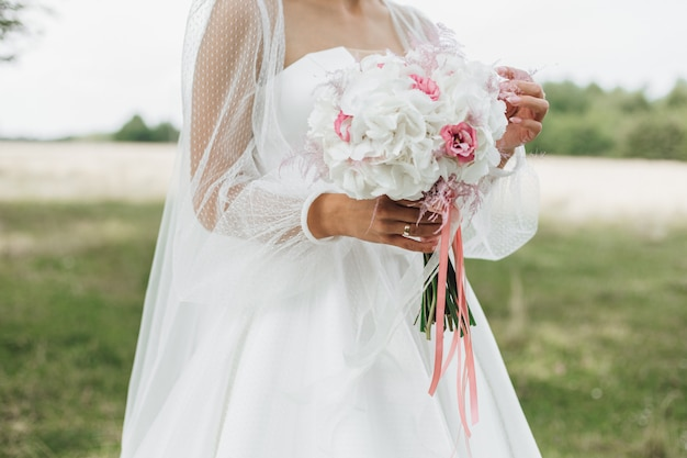 Bellissimo bouquet da sposa fatto di narcisi bianchi con rosa medio nelle mani della sposa all'aperto