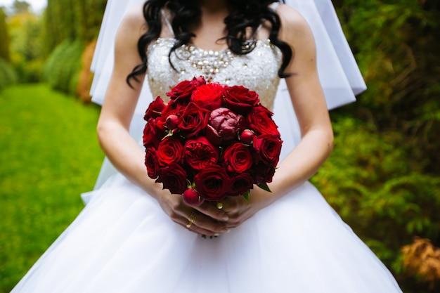 Bellissimo bouquet di colore bordeaux nelle mani della sposa in abito bianco in piedi nel parco