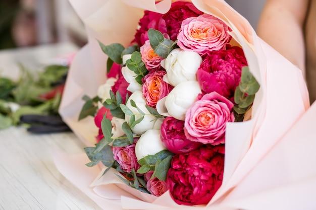 Bellissimo bouquet di peonie rosse e bianche e rose in un negozio di fiori