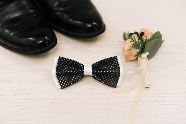 Bellissimo boutonniere con una rosa in stile rustico si trova con un papillon e scarpe da uomo su uno sfondo bianco. sposo del mattino