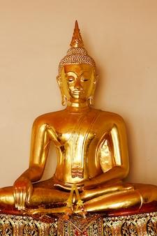 Bellissimo buddha d'oro sul piedistallo, alcune pareti bianche