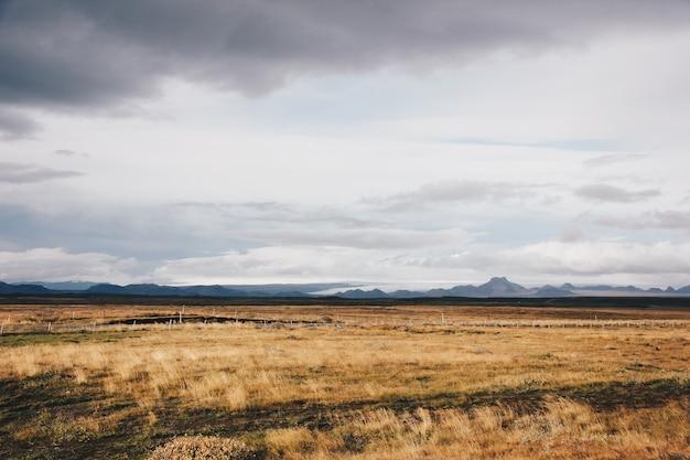 Bellissimo campo con alte montagne e colline