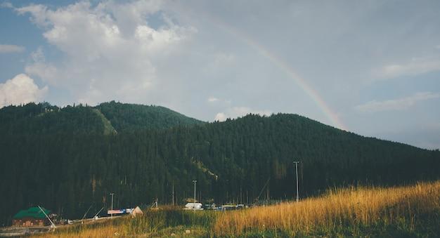 Bellissimo campo giallo in montagna con arcobaleno