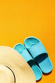 Bellissimo cappello di paglia con flip flops blu su sfondo vivace vibrante giallo. vista dall'alto. lay lay. concetto di vacanza di viaggio di estate.