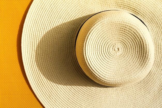 Bellissimo cappello di paglia su sfondo giallo vivace vivace. vista dall'alto. concetto di vacanza di viaggio di estate.