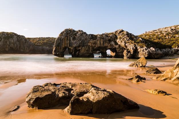 Bellissimo colpo di archi di roccia naturale vicino alla spiaggia di sabbia in una giornata di sole