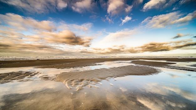 Bellissimo colpo di mare con stagni d'acqua sotto un cielo blu