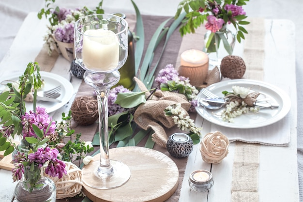 Bellissimo elegante tavolo decorato per le vacanze - matrimonio o san valentino con posate moderne, fiocco, vetro, candela e regalo