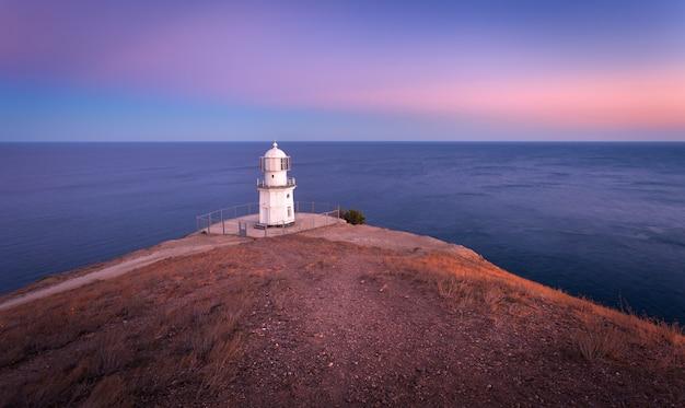 Bellissimo faro bianco sulla costa dell'oceano al tramonto