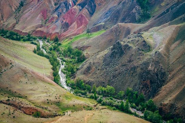 Bellissimo fiume di montagna e alberi verdi nella valle tra colline multicolori
