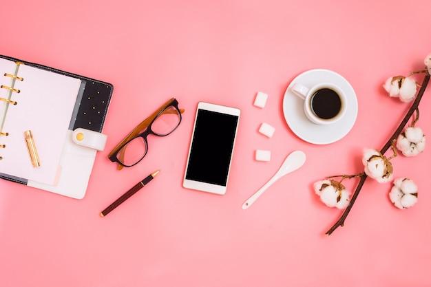 Bellissimo flatlay con tazza di caffè espresso, ramo di cotone, zollette di zucchero, smartphone e agenda