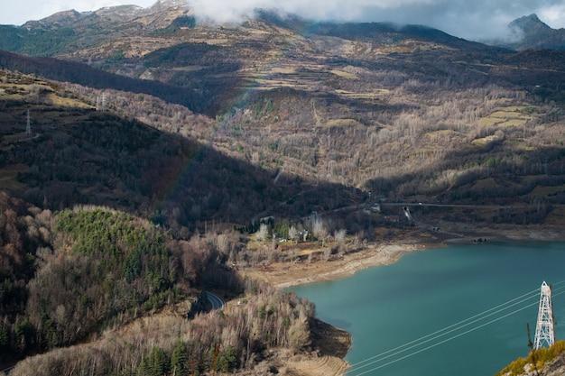 Bellissimo lago circondato da alte montagne rocciose sotto un cielo nuvoloso