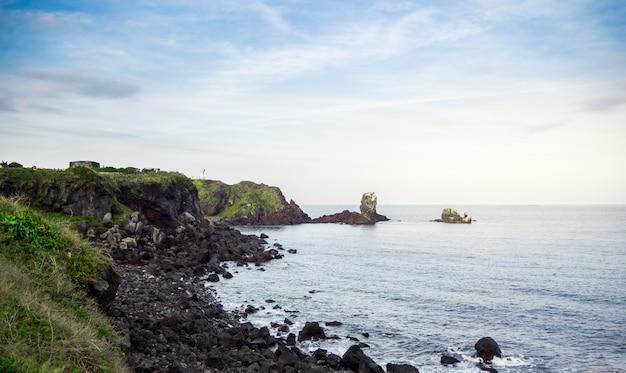 Bellissimo mare blu con spiaggia di sabbia nera e cielo dell'isola di jeju in coreano