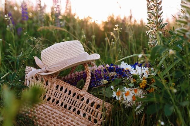 Bellissimo mazzo di lupini si trova in una borsa con un cappello di paglia sull'erba nel campo.