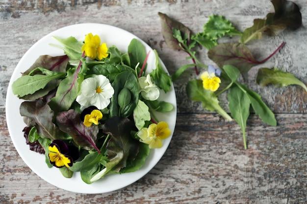 Bellissimo mix di insalate con fiori su un piatto bianco. concetto di dieta. nutrizione per ragazze. cibo vegano sano.