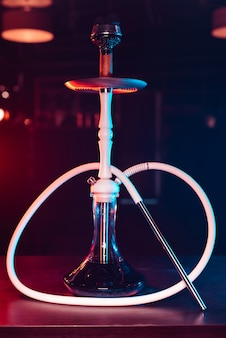 Bellissimo moderno shisha bianco con una boccetta di vetro e una ciotola di metallo con carboni