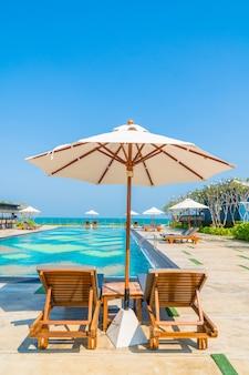 Bellissimo ombrellone e sedia intorno alla piscina in hotel e resort