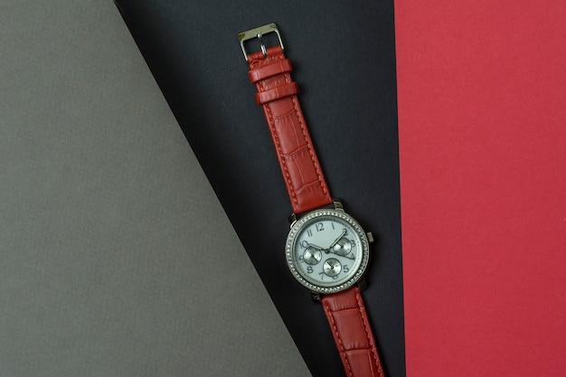 Bellissimo orologio da donna con cinturino rosso. le lenzuola grigie e rosse si posizionano sopra lo sfondo nero.