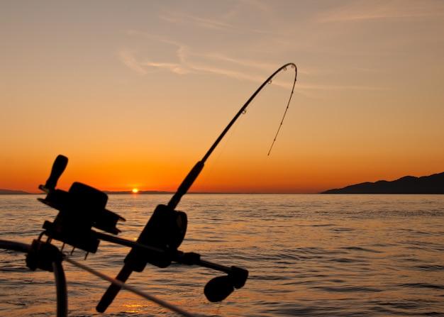 Bellissimo paesaggio al tramonto con una canna da pesca