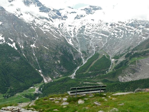 Bellissimo paesaggio delle alpi con panca in legno
