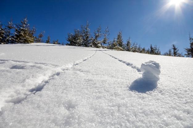 Bellissimo paesaggio invernale di natale. pendio ripido della collina della montagna con il percorso di pista umano in neve profonda cristallina e abeti verdi verdi, sole luminoso bianco che splende su chiaro cielo blu
