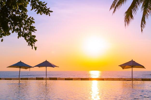 Bellissimo paesaggio piscina all'aperto con ombrellone e sdraio in hotel resort per relax tra