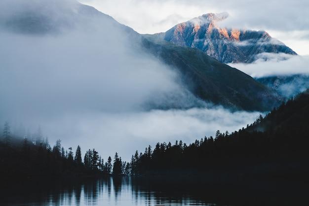 Bellissimo picco soleggiato all'alba sopra siluette della foresta di conifere.