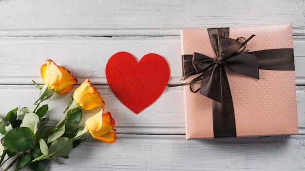 Bellissimo regalo confezionato e in legno rosa su uno sfondo bianco.