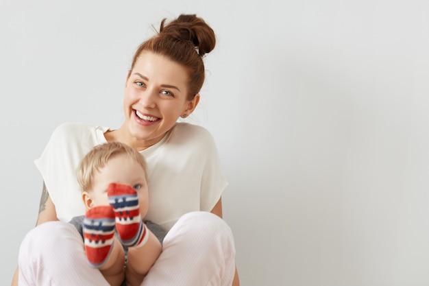 Bellissimo ritratto della madre sorridente e un bambino seduti insieme sul muro bianco. felice donna europea in abiti bianchi sorridendo e tenendo il figlio in calzini colorati sulle gambe.