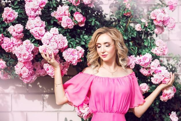 Bellissimo ritratto di una donna bionda in rose rosa. primo piano, trucco, ciglia estese