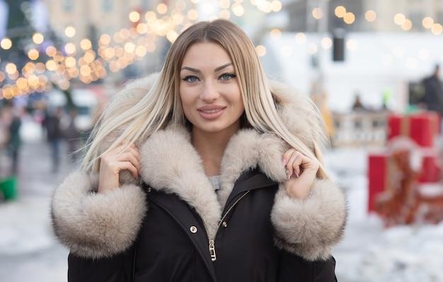 Bellissimo ritratto invernale di giovane donna nel paesaggio invernale innevato