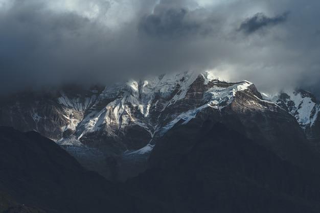 Bellissimo scatto della montagna dell'himalaya tra le nuvole