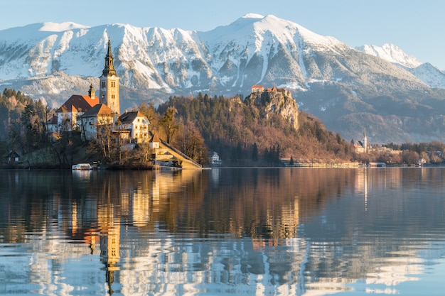 Bellissimo scatto di una casa vicino al lago con il monte ojstrica a bled, in slovenia